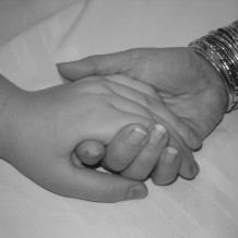 Black and white image of 2 people holding hands.