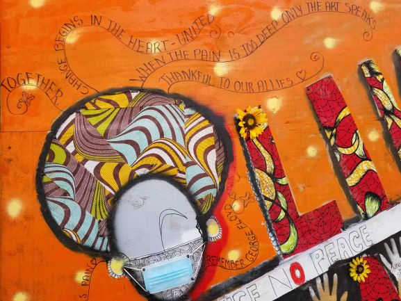 Fabric cutouts create the image of a black woman's head on an orange background. A few lines of poetry radiate from her head, urging peace and united confrontation together.
