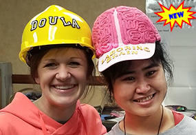 Laboring Brain - two women wearing hats - Doula hardhat and laboring brain hat.png