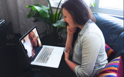 Two Women Video Chatting with laptop, window in background