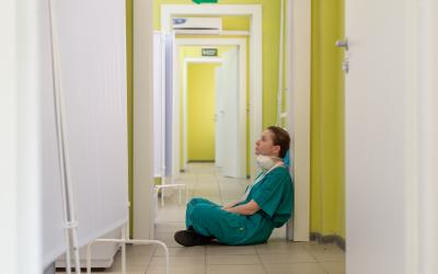 Woman in blue scrub suit sitting on floor of hospital corridor