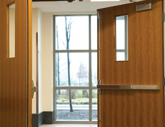 Wood double doors in hospital are partially open showing a window to the outdoors. - png